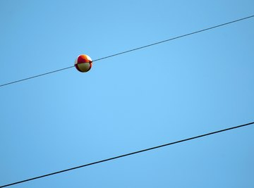 A red ball on a power line.