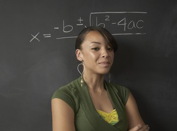 A young teacher is standing in front of her chalkboard with a math equation written on the border.