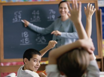Young students raising hands in math class.