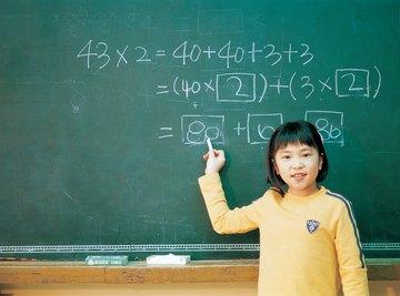 Singapore student practicing math problem on chalkboard