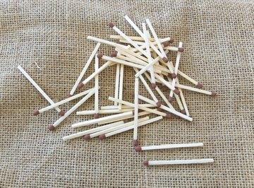 An overhead view of matchsticks on linen fabric.