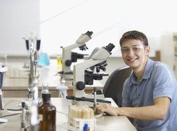 A young man in a science class sitting behind a microscope wearing glasses.