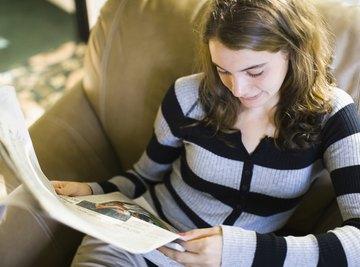 Teenage girl reading a newspaper.