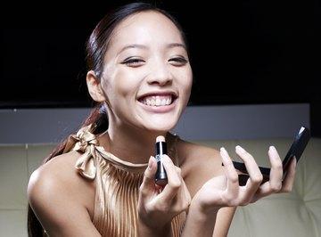 A woman applying lipstick.
