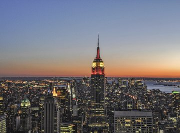 The Empire State Building aglow at night in New York City cityscape.