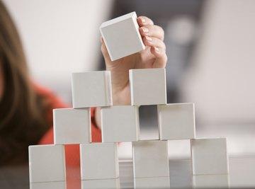 Small student making pyramid with blocks