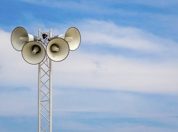 A tower with loudspeakers against a summer sky.