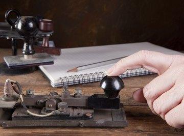 Hand using an antique telegraph machine.