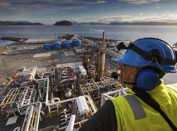 An employee looking over an oil drilling facility.
