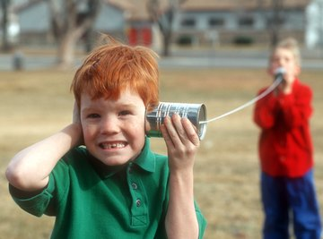 Two boys using cans and string as walkie-talkies