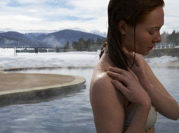 A woman stepping out of a hot spring in the mountains.
