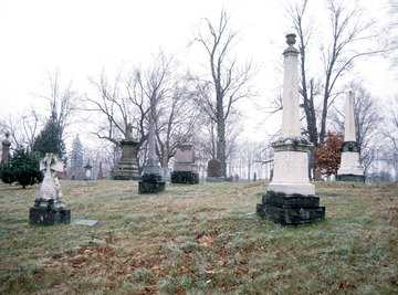 Acid rain reacts chemically with marble and limestone grave markers, pitting the stone and making details unclear.