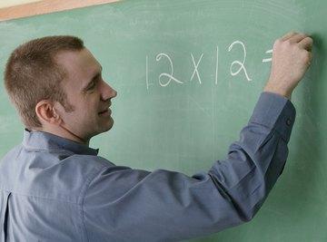 Teacher writing multiplication on board.
