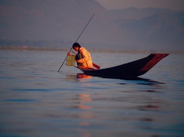 Silhouette of man spear fishing off small boat