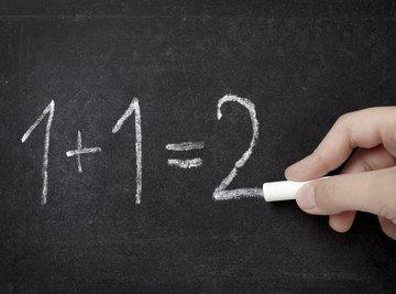 Hand writing math problem on chalkboard