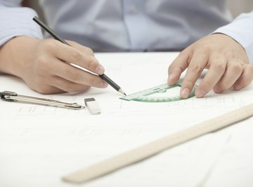A close-up of an architect using a protractor at his desk.