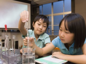 Two kids playing with laboratory gear like beakers and test tubes.