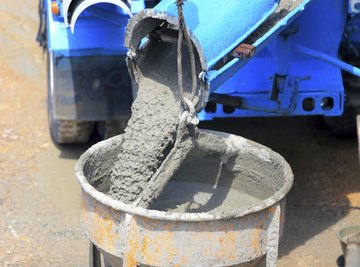 Wet cement pours out of a cement trunk mixer into a barrel