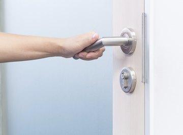 A woman grabs a door handle.