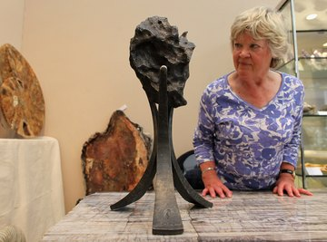 A woman examines a meteorite on display at an art house.
