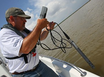 An environmentalist testing the salinity level of a body of water from a boat.