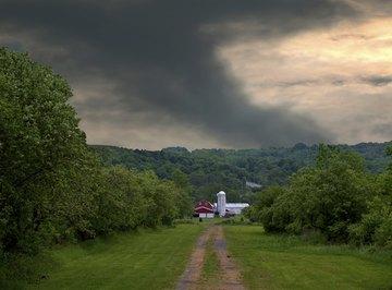 A tornado behind a farm.