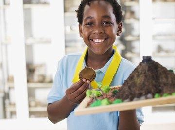 Black boy holding award-winning volcano science project.