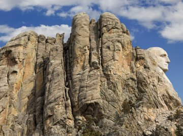 The granite rock of the Mount Rushmore National Memorial shows many stages of weathering.