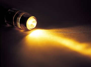 The flow of electrons from zinc to copper produces enough current to power a small flashlight bulb.