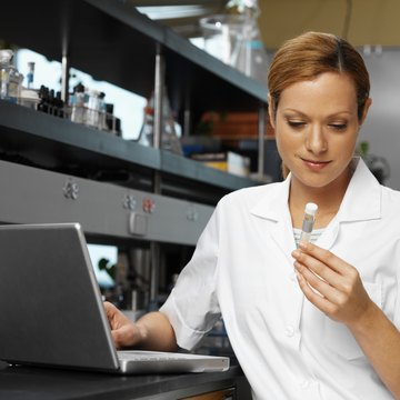 Young female microbiologist working on a laptop looking at a test tube