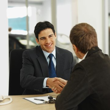 Close-up of salesman and customer shaking hands in office