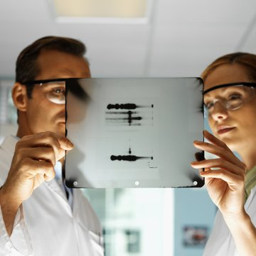 Portrait of young microbiologists holding an x-ray film with a dna pattern