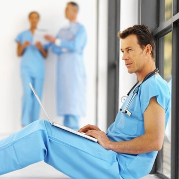 Close-up of a mid adult surgeon sitting on the floor working on laptop with two other medical personnel in background