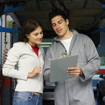 Male mechanic with a clipboard explaining a problem to a female customer in a garage