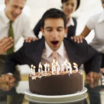 businessman blowing out candles on a birthday cake