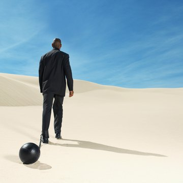 businessman wearing ball and chain in desert rear view, low angle view