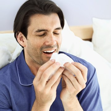 Close-up of a young man sneezing into a tissue