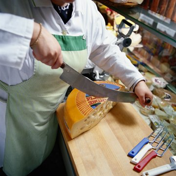 Woman Slicing Cheese in a Delicatessen