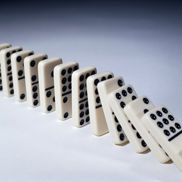The domino theory suggested communism would spread like a line of dominoes.