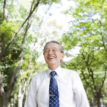 Senior businessman in park smiling