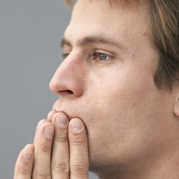 Mid adult man looking away with hands on mouth, close-up