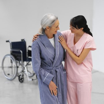 Front view of a young nurse helping mature woman to walk