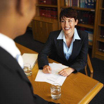 businesswoman sitting behind a desk smiling at a person in front of her