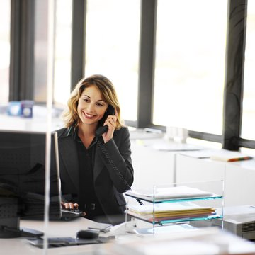 portrait of a businesswoman sitting in an office talking on the phone