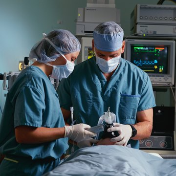 Surgeon and anesthetist looking at patient on operating table