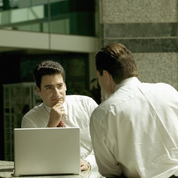 Two businessmen having a meeting and using laptop