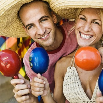 Tourists hold maracas and wear sombreros