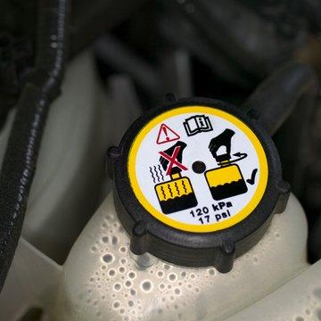 Cap on coolant overflow reservoir in car engine