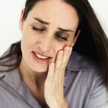 Young woman holding side of face in pain