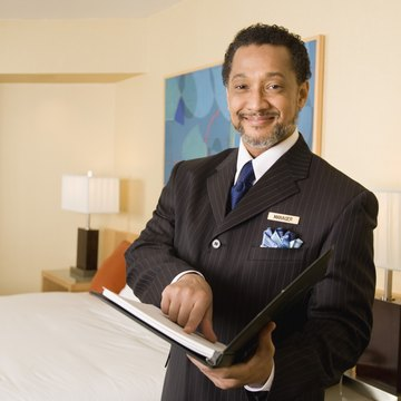 Hotel Manager Pointing To Notebook